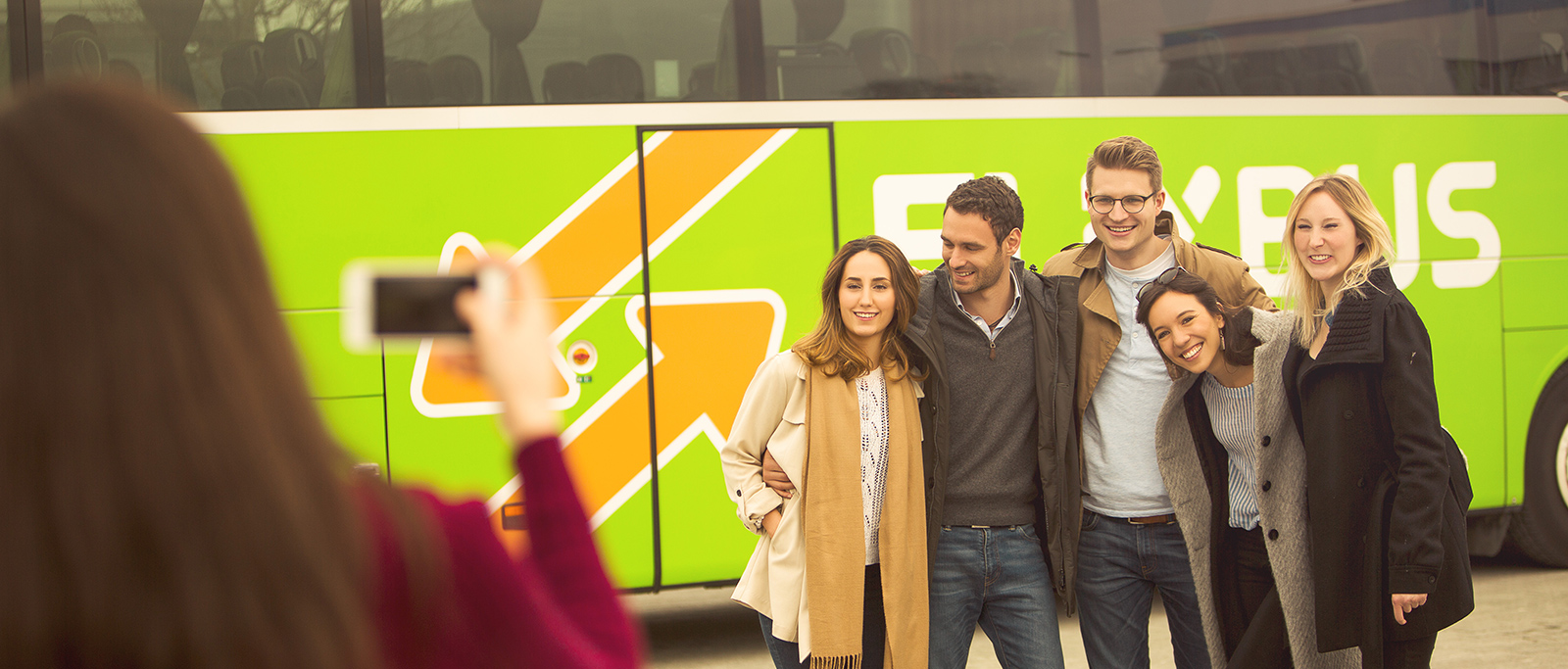 Group of friends in front of a FlixBus